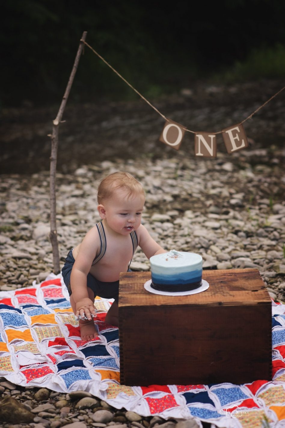 one year old boy at the creek for first birthday pictures