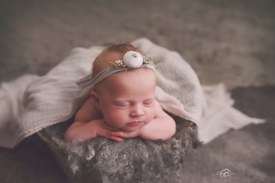 Newborn girl with grey set up and headband