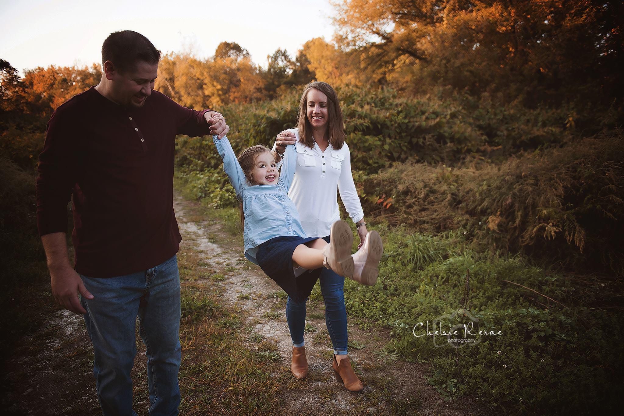 family swinging little girl laughing